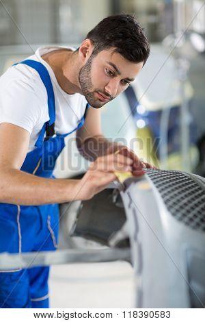 auto mechanic polishing car in service