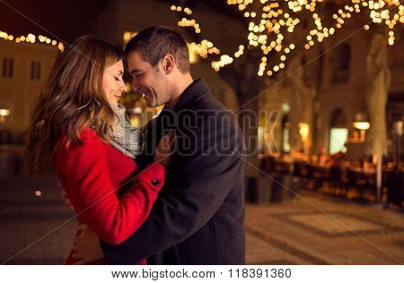 Young happy attractive amorous couple embracing  and kissing outdoor poster