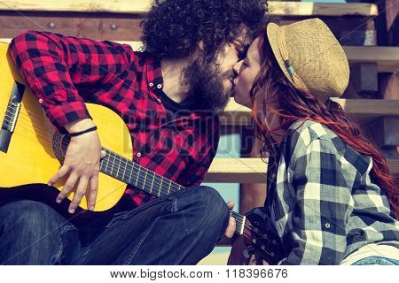 Young couple with guitar kissing in outdoors