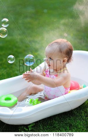 Little Girl Bathes In A Bath With Soap Bubbles