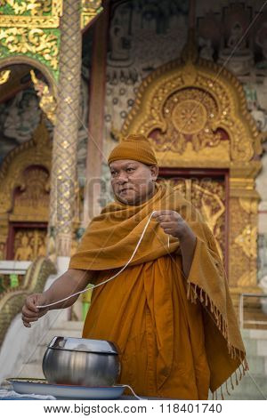 Monk with Sai Sin bracelet to give blessing