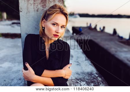 Girl hugging himself on background of concrete and the river at sunset.