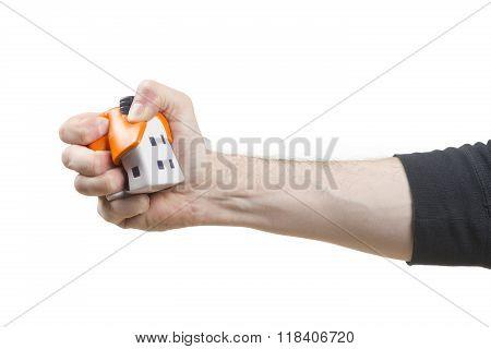 Male hand sqeezing a Stress ball house