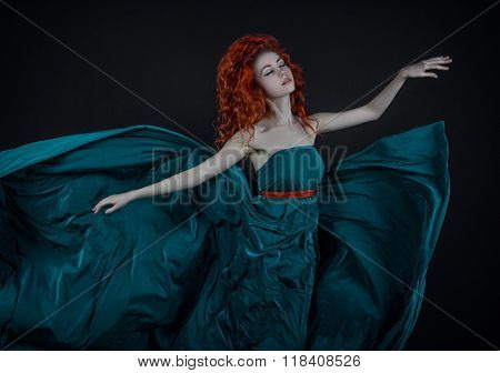 Girl In A Silk Dress, A Beautiful Red-haired Girl Dancing In A Long Green Dress Flying In The Air, A