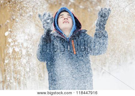Happy teenager trowing snow