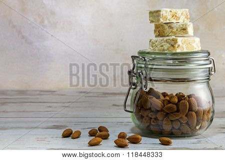 Torrone Or Nougat On A Glass Jar With Almonds On Bright Rustic Wooden Background With Copy Space