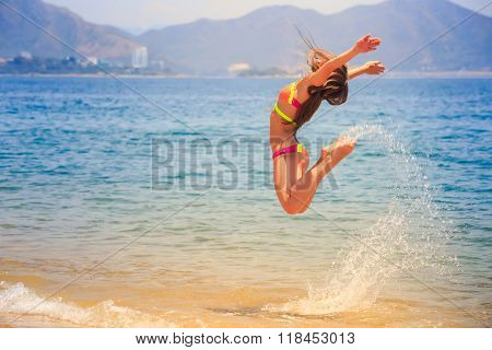 blonde slim female gymnast in bikini side view in flying jump with bent knees over sea and splashes against hills poster