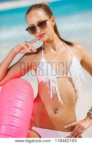 The beautiful woman in bikini with a pink lifebuoy