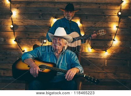 Two Smiling Senior Country And Western Musicians Sitting On Chair In Front Of Wooden Wall With Light