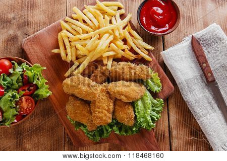chicken wings fried in breadcrumbs with sauce and french fries