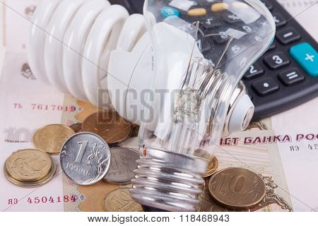 Energy saving concept. Electric light bulb, ruble money and calculator
