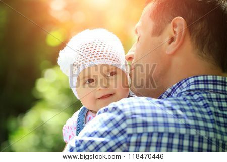 Father kissing and holding small daughter baby girl cute hazel-eyed kid tiny little child wearing white flower beanie hat outdoor sun spot summer day on blurred green background horizontal picture