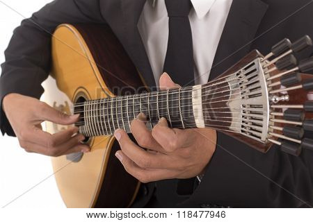 Close up shot of a man with his fingers on the frets of a portuguese guitar playing