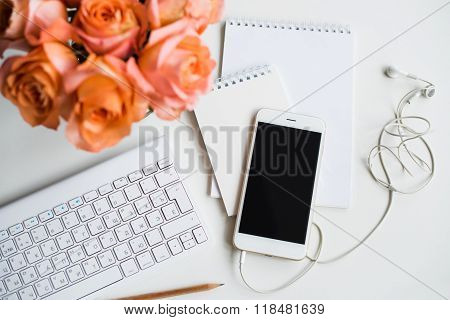 Bright white office table decor with fresh flowers, computer keyboard and smart phone. Woman's modern workspace, interior details. poster