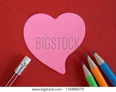 Pink Heart-shaped Memorandum On Red Paper With Colorful Pencils And Erase