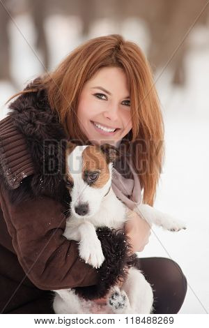Young redhead woman outdoors with cute dog - Jack Russell Terrier, winter season.