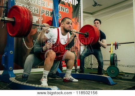 male athlete of powerlifter squats barbell