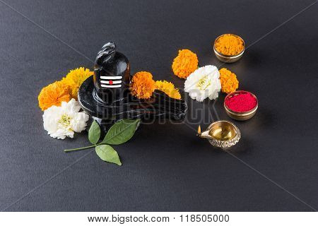 Shiva Linga made up of black stone decorated with flowers & bael leaf known as Aegle marmelos, maha