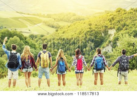 Group Of Hikers In The Mountain In Single File Holding Hands