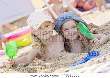 Two Little Girls Playing In The Sand