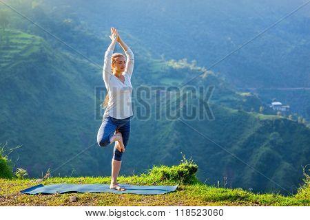 Woman practices balance yoga asana Vrikshasana tree pose in Himalayas mountains outdoors in the morning. Himachal Pradesh, India. Panorama