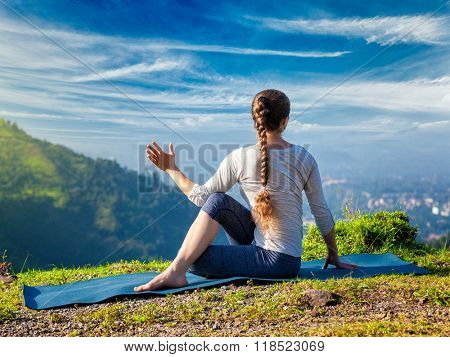 Sporty fit woman practices yoga asana Parivrtta Marichyasana -  seated spinal twist outdoors in mountains in the  morning