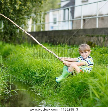 Little cute kid boy fishing on a river with selfmade fishing rod on sunny summer day. Happy child having fun. Active leisure for children outdoors.
