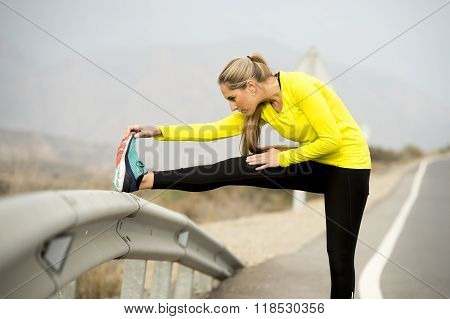 Sport Woman Stretching Leg Muscle After Running Workout On Asphalt Road With Dry Desert Landscape In