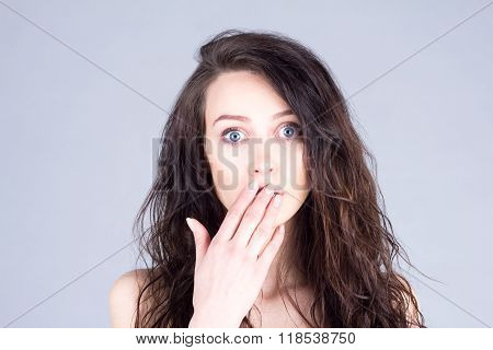 Young woman with very large eyes in surprise covers mouth with hand