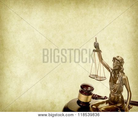 Statue of justice on old paper background with gavel, law concept