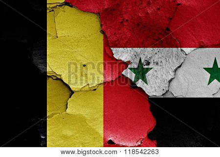 flags of Belgium and Syria painted on cracked wall