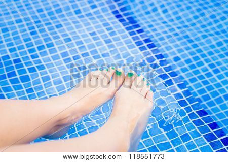 Woman Feet Relaxing In Swimming Pool