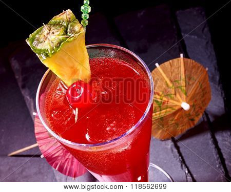 Pineapple red  cocktail with cherry and umbrella in highball glass . Top view. Food idea.