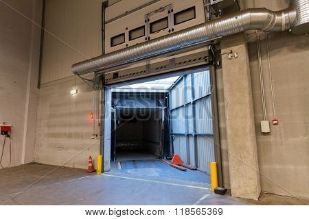 logistic, storage, shipment, transportation and loading concept - warehouse door or gate and truck container