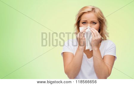 people, healthcare, rhinitis, cold and allergy concept - unhappy woman with paper napkin blowing nose over green natural background poster