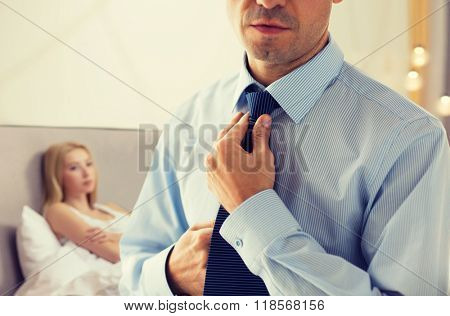 people, business, relations and problems concept - close up of man in shirt dressing up and adjusting tie on neck over woman in bed background