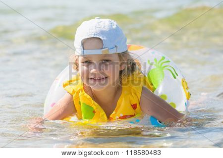 Four-year Girl Swims In The Summer With A Circle In The Sea