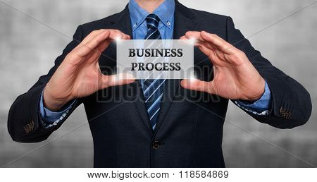 Businessman Holds White Card With Business Process Sign, Grey - Stock Photo