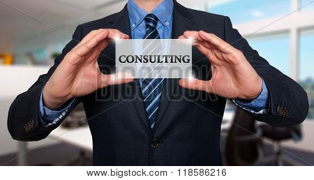 Businessman Holds White Card With Consulting Sign, Office - Stock Photo