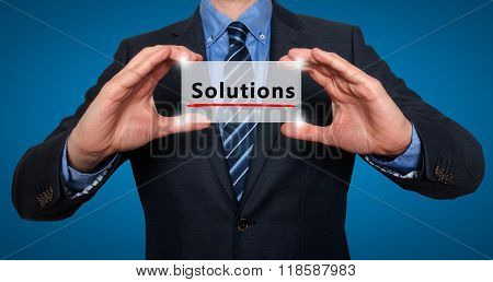 Businessman Holding White Card With Solutions Sign, Blue - Stock Photo
