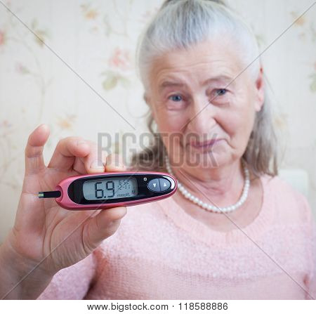 medicine, age, diabetes, health care and people concept - senior woman with glucometer checking bloo