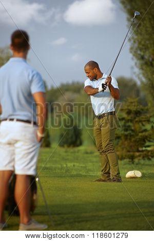 Ethnic male golfer teeing golf ball, swinging golf club.