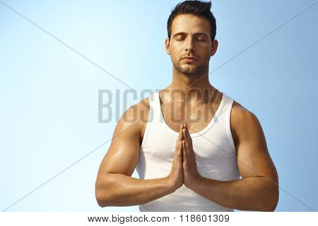 Young athletic man meditating eyes closed outdoors.