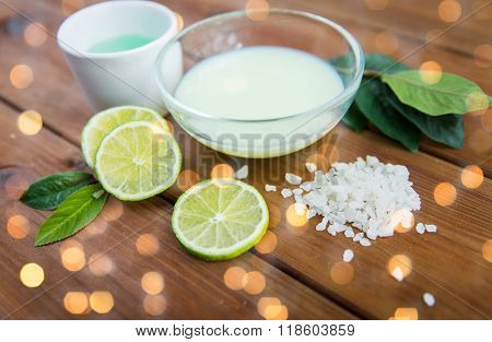 beauty, spa, body care and  natural cosmetics concept - close up of bowls with citrus body lotion, cream and sea salt on wooden table