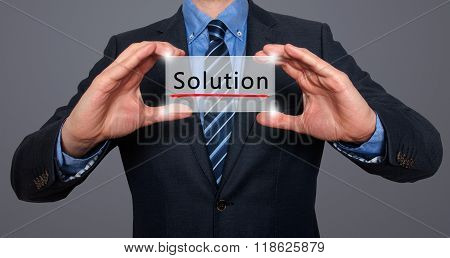 Businessman Holding White Card With Solution Sign, Grey - Stock Photo