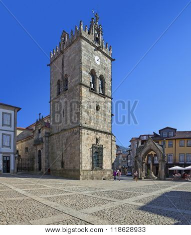 Guimaraes, Portugal - October, 2015: Locals pass by the Nossa Senhora da Oliveira Church and Salado Monument (Padrao do Salado) in Oliveira Square. Unesco World Heritage Site.