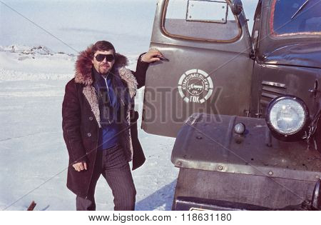 Outdoor portrait of young soviet driver near his truck