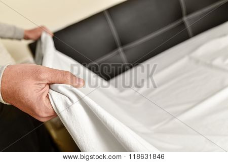 closeup of a young man extending the bedsheet on the matress as he is making the bed