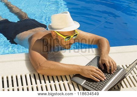 Working on laptop from the swimming pool