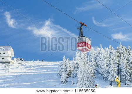 POIANA BRASOV ROMANIA - JANUARY 24 2016: Cable car cabin transports tourists from Poiana Brasov resort to Postavaru peak and ski slopes on sunny day with blue sky